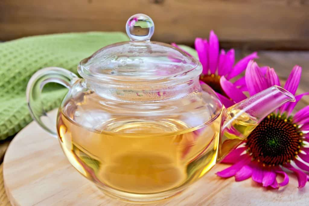 Tea from Echinacea in glass teapot on board with cloth